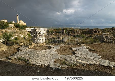 Pillar and ancient street in sunlight during storm in ruins with dramatic cloudscape with mosque in Tyre, Sour, Lebanon