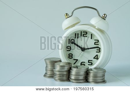 saving or time countdown concept as white alarm clock and stack of coins.