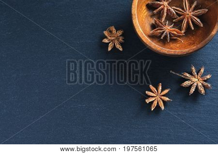 Anise star or badian on black stone background. Top view. Copyspace
