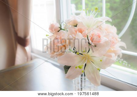 Flowers in a Glass Vase on table near window.