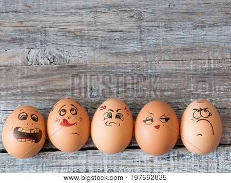 Eggs group in a box with cheerful and mischievous faces having fun. Concept of joint recreation