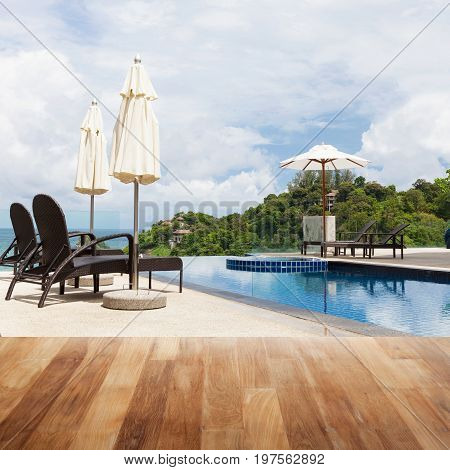 Wood table top on Beach chair in outdoor with swimming pool and sea view andaman sea