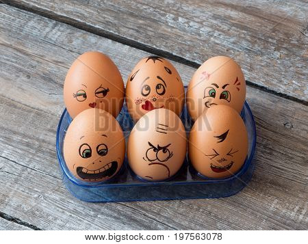 Eggs group in a carton box with cheerful and mischievous faces having fun. Concept of joint recreation