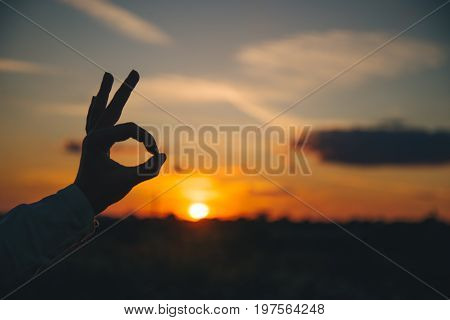 hands show ok sign on sunset, silhouette