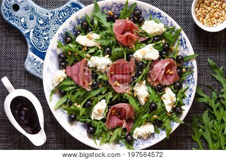 Salad With Prosciutto Arugula Soft Cheese Cedar Nuts And Black Currant