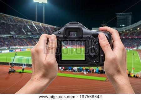 Hand holding the camera over blurred of action photographer taking photo at player in Abstract blurred photo of soccer stadium sport background concept