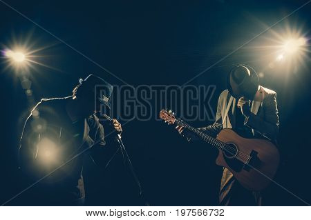 Musician Duo band hand holding the microphone and singing a song and playing the guitar on black background with spot light and lens flare musical concept