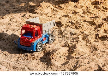 Red Toy Truck Covered in Sand in Children Sandbox Playground