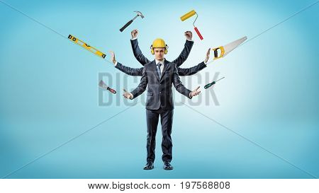 A businessman with many hands that wears a hardhat surrounded by construction instruments. Multitasking. One man for all tasks. Jack-of-all-trades.