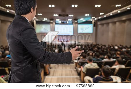 Rear view of Business People Conference Speaker on over the Abstract blurred photo of conference hall or seminar room with attendee background business seminar and education concept