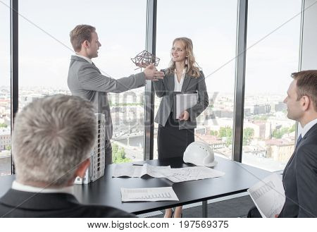 Business meeting of architects and investors discussing new construction shapes at presentation model of modern multi storey residential building house on table