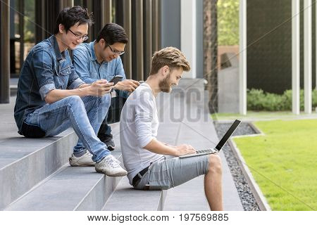 Group Of Asian and Multi-ethnic young business people in casual clothes working outside on steps with technology equipment with happy action. People business group concept.