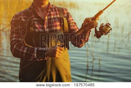 A fisherman in a red shirt is fishing for spinning in a freshwater pond at sunset.