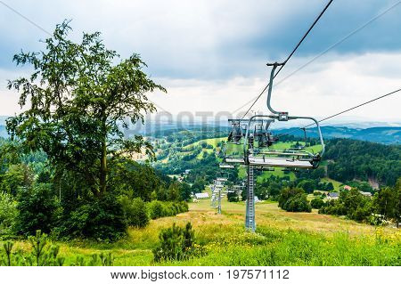 Chair lift on summer. The view from top to down to the valley. On background are heavy clouds mountains.