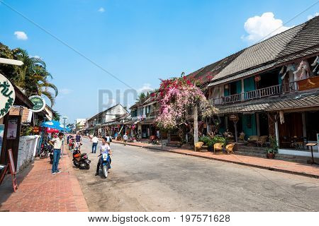 LUANG PRABANG LAOS - MARCH 11 2017: People Restaurants and stores at Sisavangvong Road located in the olf Quarter of Luang Prabang Laos.