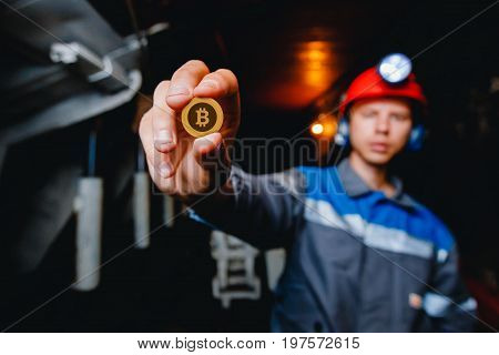 miner in a mine holds a bit of crycoin in his hand. Concept mining crypto currency of ETH Ethereum.