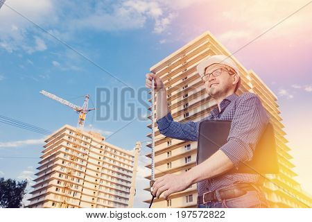 Male construction builder worker - foreman is engineer in protective helmet, glasses on background building a house with crane Ruler measures. Concept calculation of construction time, cost.