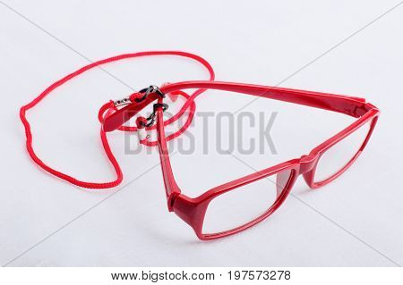 Red reading glasses with red neck strap attached on a white surface.