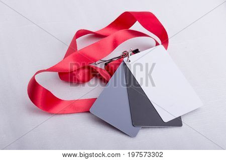 Three cards one white one grey and one black attached together and on a red strap on a white surface.