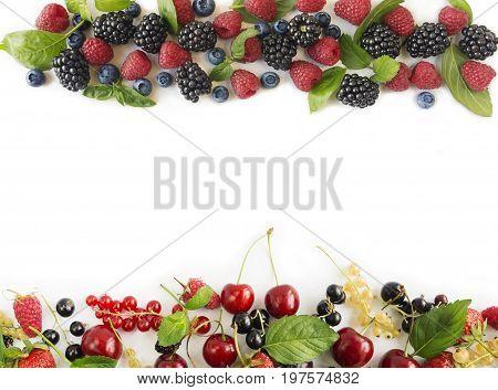 Ripe raspberries blueberries blackberries redcurrants blackcurrants mulberries and cherries on white background. Berries at border of image with copy space for text. Background berries. Various fresh summer berries.