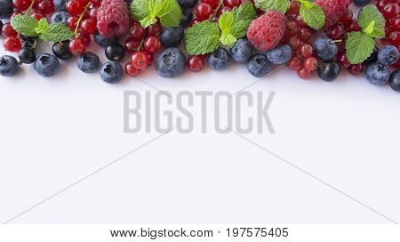 Ripe raspberries blueberries blackcurrants and red currants mint. Berries at border of image with copy space for text. Background berries. Top view. Various fresh summer berries on white background.