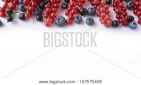 Ripe blueberries blackcurrants and red currants. Berries at border of image with copy space for text. Background berries. Top view. Various fresh summer berries on white background.