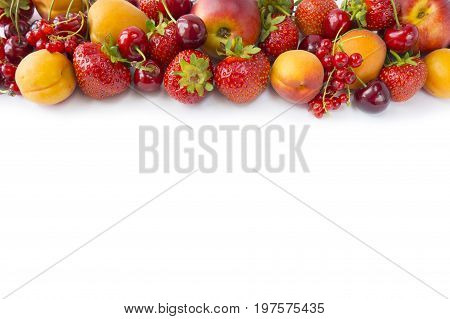 Various fresh summer berries. Top view. Ripe strawberries redcurrants apricots nectarines and cherries on white background. Berries at border of image with copy space for text. Background berries.