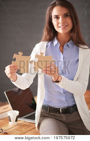 Business woman holding and pointing to a puzzle piece. Concept team. Woman. Puzzle.