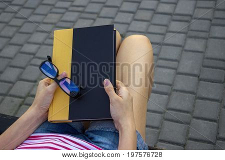 The girl on a bench in the park with a book and glasses in her lap. A student reading a book in the park