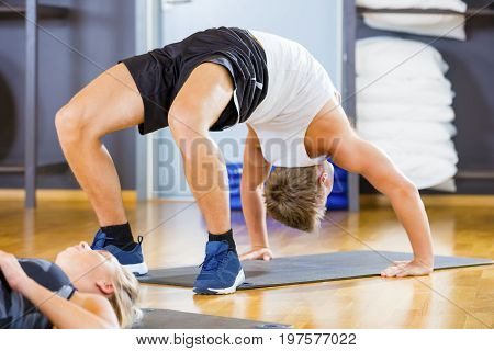 Full frame shot of young man performing backbend pose on mat in gym