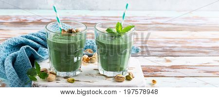 Two glasses of healthy green smoothie with mint, pistachios and spirulina on old wooden background. Detox, diet, healthy, vegetarian food concept with copy space.
