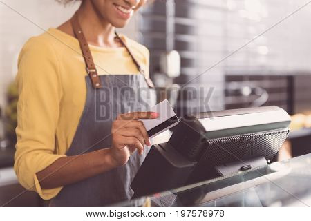 Thanks for your purchase. Positive african woman cashier is paying for order by credit card while standing at cash desk in cafe. Copy space in the right side