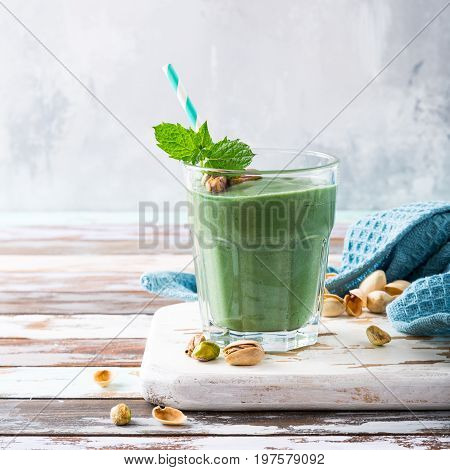 Healthy green smoothie with mint, pistachios and spirulina in glass on old wooden background. Detox, diet, healthy, vegetarian food concept with copy space.