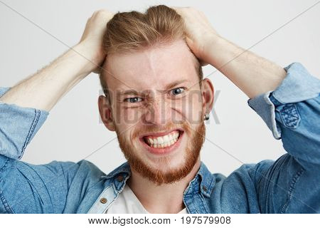 Close up of angry rage young man touching his hair looking at camera clenched teeth over wite background. Copy space.