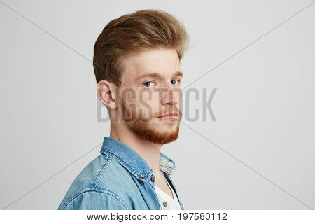 Close up portrait of young handsome hipster man with beard wearing jean shirt looking at camera over white background. Copy space.