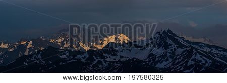 Sunset high in mountain. Mounts Zakzan-Syrt and Pshish. Greater Caucasus Mountain Range. Karachay-Cherkessia. Russia.