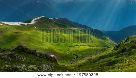 Green river valley in beams of evening sun. Caucasus mountains. Karachay-Cherkessia. Russia.