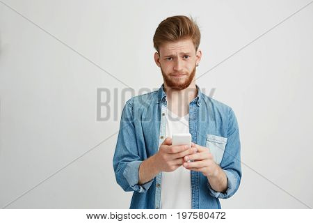 Dissapointed upset young man with beard holding smart phone looking at camera over white background. Copy space.