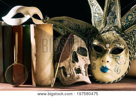 Theater and drama concept. Human skull venetian masks with old scroll book magnifying glass and quill on wooden table