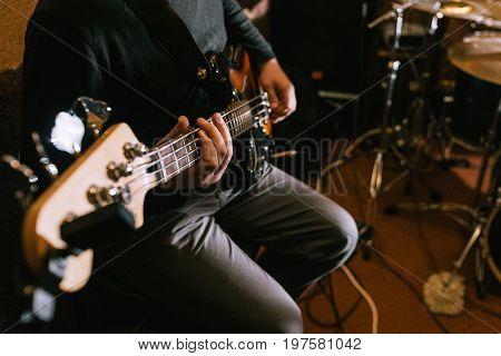 Guitarist playing bass guitar in studio closeup. Music band recording process, live rock concert