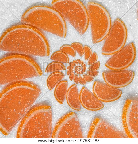 Abstract fruit jelly wedges orange cantle lobule on white sugar background. Orange jellies. Sweet fruit segments. Juicy fruit jelly on sugar sand Abstract food fractal Exotic sweets pattern background