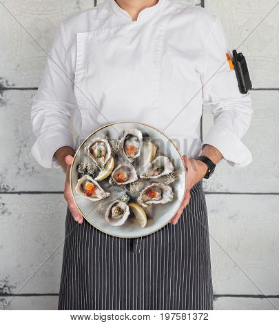 Chef holds a plate of oysters upright