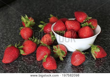 Red Strawberries In A White Bowl And On A Table.