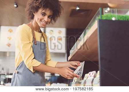 Great choice. Low angle portrait of delightful cute female worker is standing near shelves with foods in specialized store and looking at camera with joy. Copy space in the right side