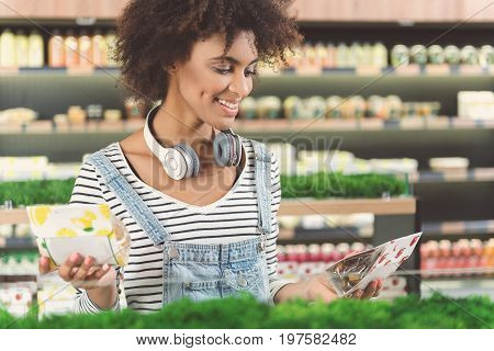 Which is better. Positive young woman is standing in vegan supermarket and choosing healthy foods. Shelves with wide assortments of vegetarian products on background. Copy space in the right side