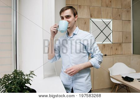 Breake from work. Smiling man with cup of coffe take a pause from work in modern office
