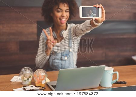 Say cheese. Selective focus of screen of smartphone on selfie stick with funny joyful girl which is holding it on wooden background. She is sitting in organic cafe with vegetarian food