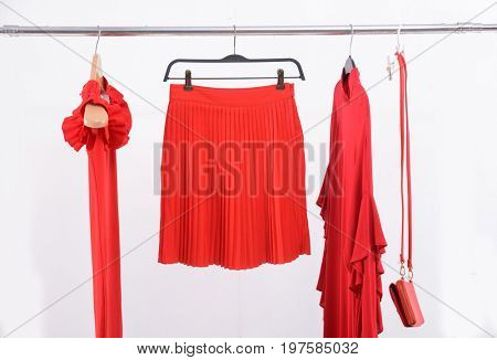 Red flared skirt and shirt ,bag, sundress on clothes rack isolated