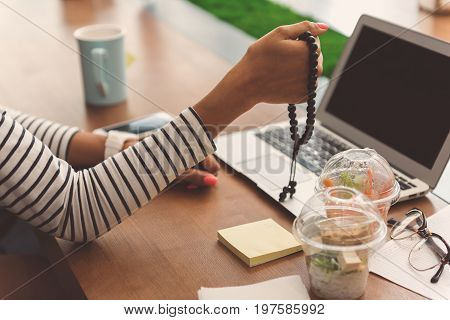 Close-up of arms of stylish girl which is sitting in organic cafe with vegetarian food and modern laptop. She is holding black rosary in her hand