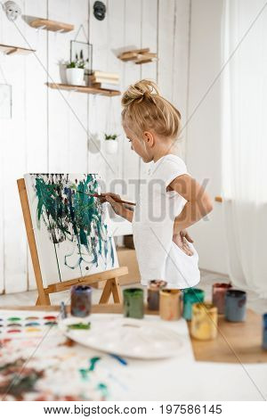 Shot of beautiful little European girl having concentrated look while working on her picture in art room. Drawinng blonde female child in white t-shirt standing behind easel. Kids art activities.
